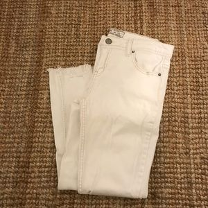 White distressed jeans with tan stitching.